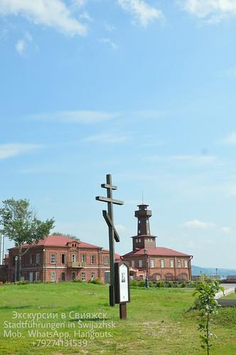 Свияжск, памятный крест на месте разрушенного храма. На заднем плане: здание бывшего пожарного обоза