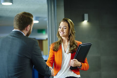 A young female job candidate is shaking hands with her prospective employer. She is smiling confidently and looking him in the eye . She is holding her cv resume . they are both standing in a modern office interior.