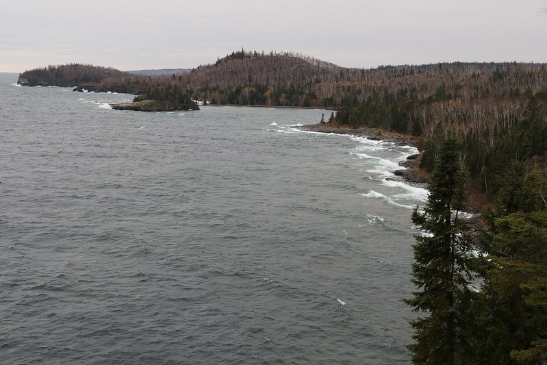 coastline viewed from above, with a small island in the distance, white lines marking waves reaching shore