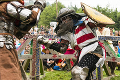 Participants of the festival in knight armor arrange fights