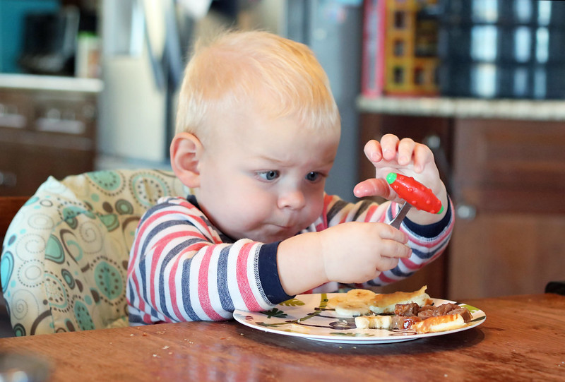 Jonathan learning to use a fork and spoon