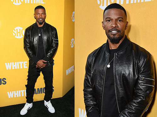 Jamie-Fox-wearing-a-black-leather-bomber-jacket-with-white-trainers