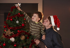 Dad helping boy to decorate christmas tree