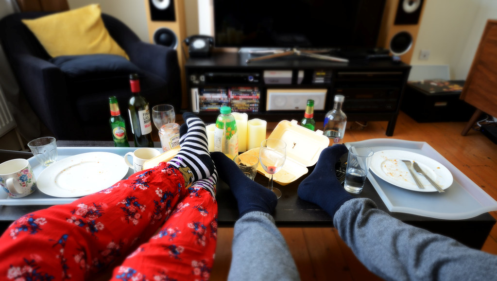 Dr Adam's image, called 'Misery Loves Company', showing two student's legs, in pyjama bottoms, resting on a coffee table amid empty bottles, dirty plates and takeaway food boxes
