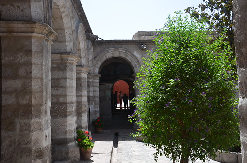 Unbemalte Mauern und Pfeiler auf der linken Seite, ein Baum auf der rechten Seite, hinten andere Besucher.