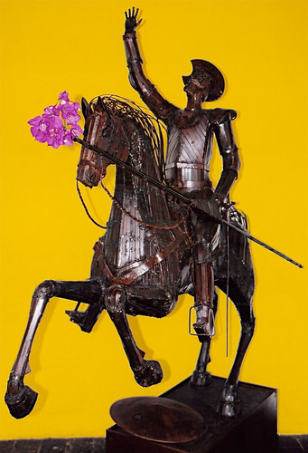 A metal sculpture of the most famous knight, Don Quixote, in Guatemala with a cluster of pink Bougainvillea flowers stuffed on the end of his lance