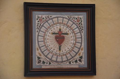 Ein Kreuz in einem Kreis mit einem Herz im Zentrum, Oben kommen Flammen aus dem Herz.