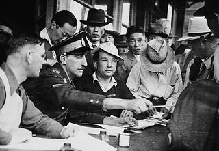 Royal Canadian Mounted Police constable checks documents of Japanese-Canadian evacuees, Slocan City, British Columbia / Gendarme de la Gendarmerie royale du Canada vérifiant les documents d'évacués d'origine japonaise, Slocan (Colombie-Britannique)