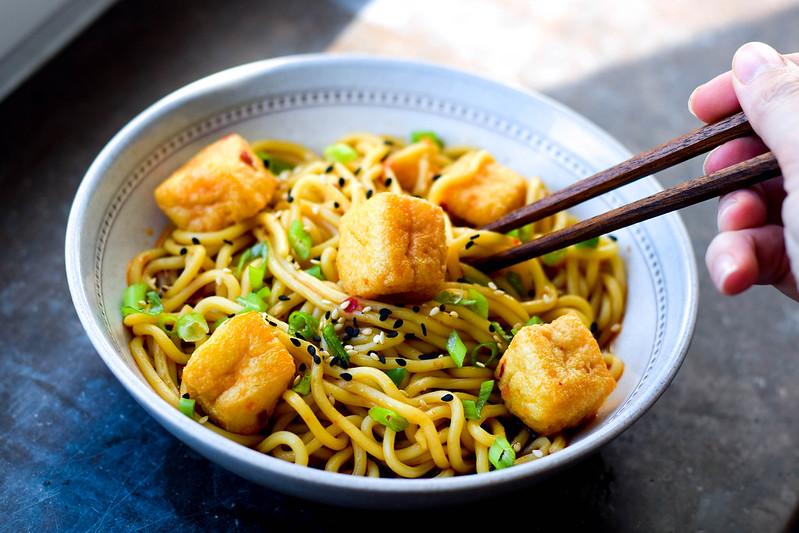 En ljusgrå skål fylld med nudlar i sesamsås, puffad tofu, hackad vårlök och sesamfrön. En hand håller i ett par ätpinnar