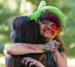 Cheerful girls in color powder  hugs