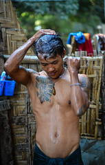 A Burmese young man bathing at house