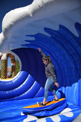 """Student tries her hand at """"surfing"""" during the Red and White Week Kick-Off on Stafford Commons."""