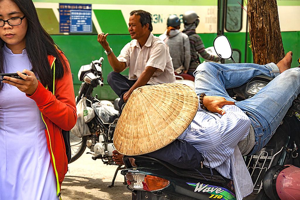 Man sleeping on motorbike--Saigon