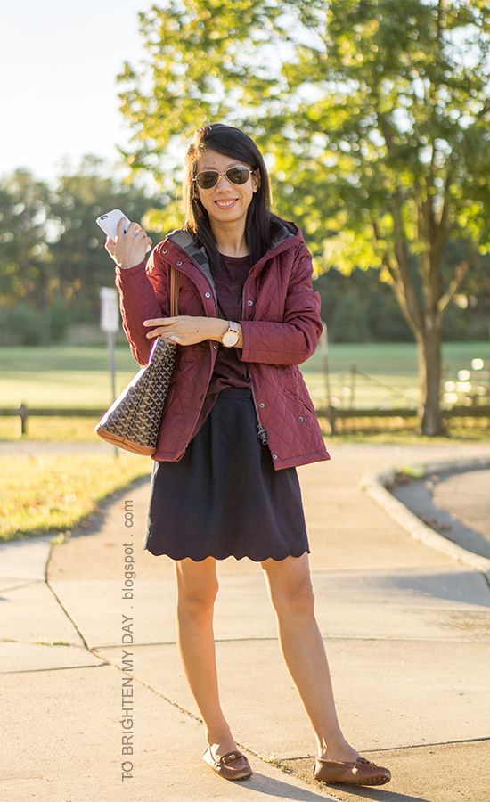 red quilted jacket, burgundy striped top, navy skirt with scallop hem, oversized watch, monogrammed tote, brown loafers