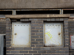 "Two lockable metal cabinets embedded in a grey brick wall.  The one on the right has ""CINATRA'S"" painted on it."