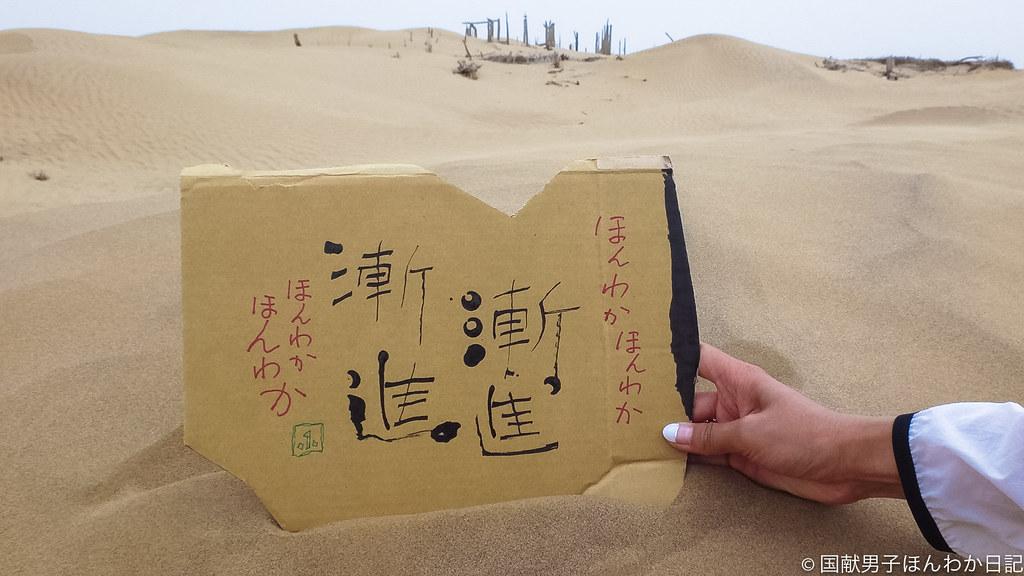 小僧落書きを尹暢天津TVキャスターに持ってもらい、背景はニヤ遺跡(撮影:筆者)