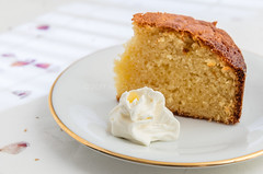 Piece of yellow cake with whipped cream.