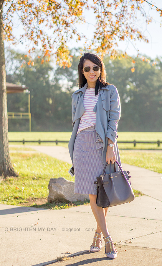 gray draped trench coat, pink striped top, gold watch, striped seersucker pencil skirt with bow, gray tote, watercolor studded flats