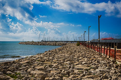 Bright sea pier  with colorful clouds over azure waters