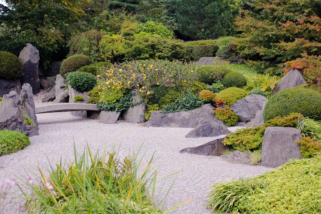 The Japanese Garden at Kew Gardens, London, with neatly arranged sand, rocks and flowers, passed by a tiny stone bridge