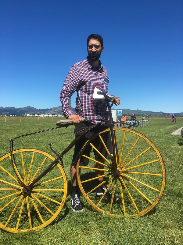 Man holds yellow 1865-era bicycle on airfield