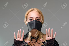 Woman with self-adhesive tape over her mouth