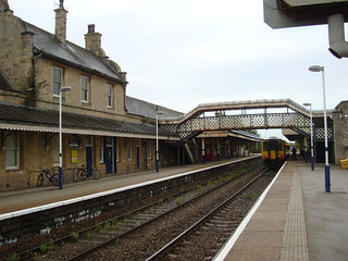 Worksop railway station buildings and footbridge, with a class 156 train