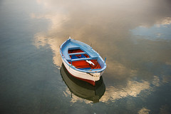 Beautiful picture of a boat with a cloudy reflection
