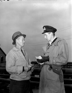 An officer of the Royal Canadian Naval Volunteer Reserve (RCNVR) examines the papers of a Japanese-Canadian fisherman... / Agent de la Réserve de volontaires de la Marine royale du Canada examinant les papiers d'un pêcheur canadien d'origine japonais