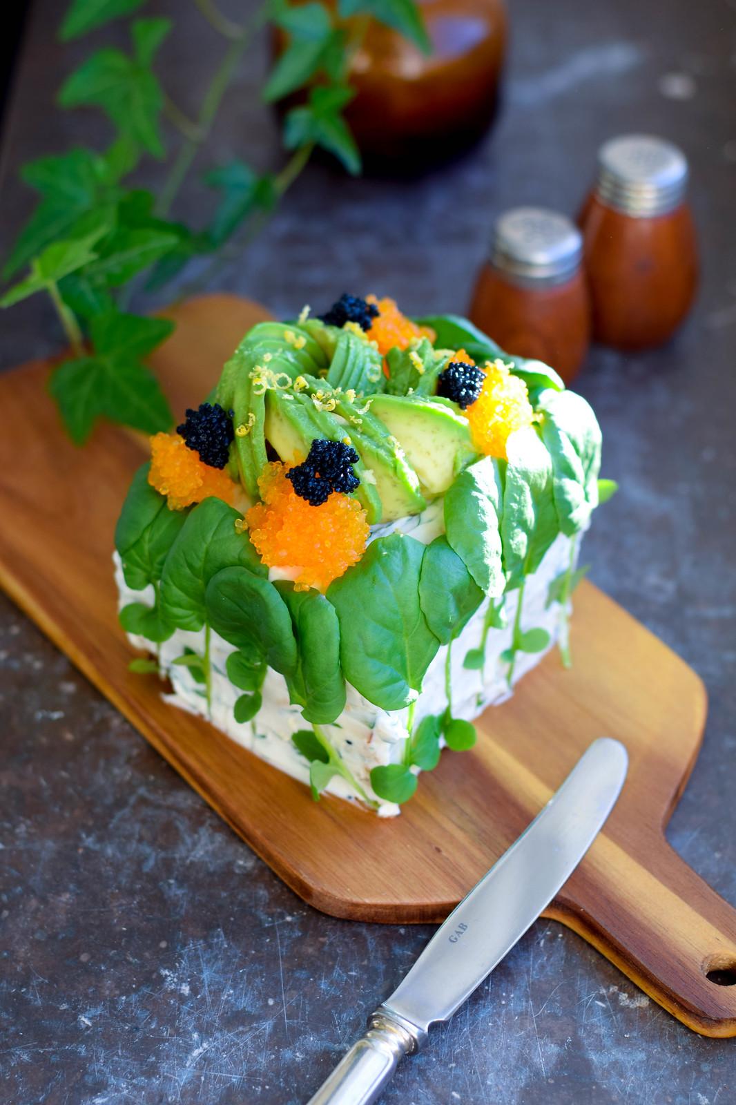 En bit vegansk smörgåstårta dekorerad med en avokadoros och tångrom står uppställd på en träskärbräda på en mörk marmorbakgrund