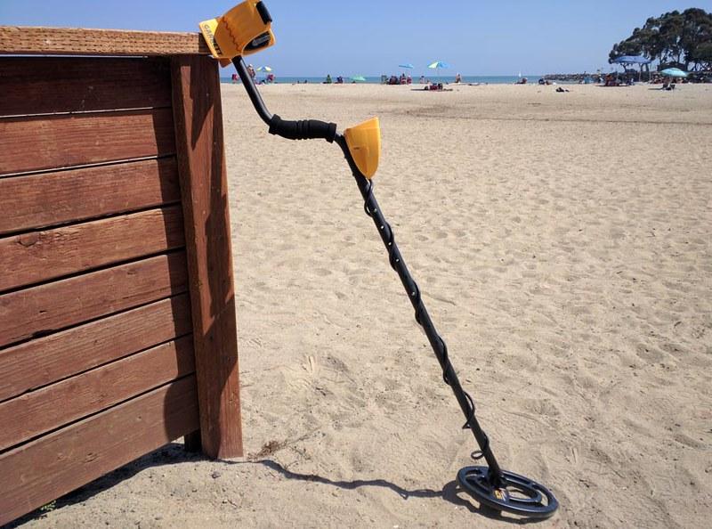 Garrett Ace yellow and black metal detector at a beach