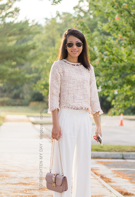 light pink tweed top with pearls, gold jewelry, white wide-legged pants, nude bag