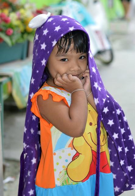 shy girl underneath a cape