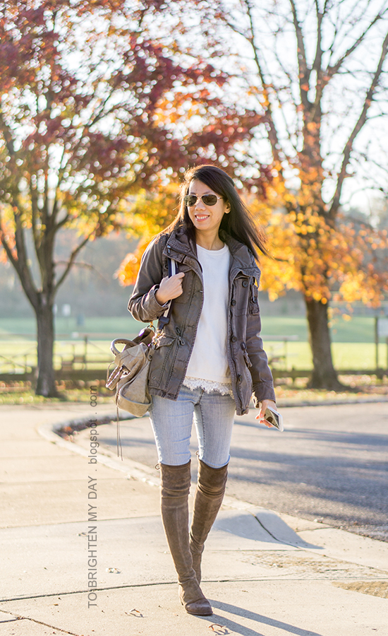 gray military jacket, white sweater with lace hem, light wash skinny jeans, gray tote with stripe strap, gray suede over the knee boots