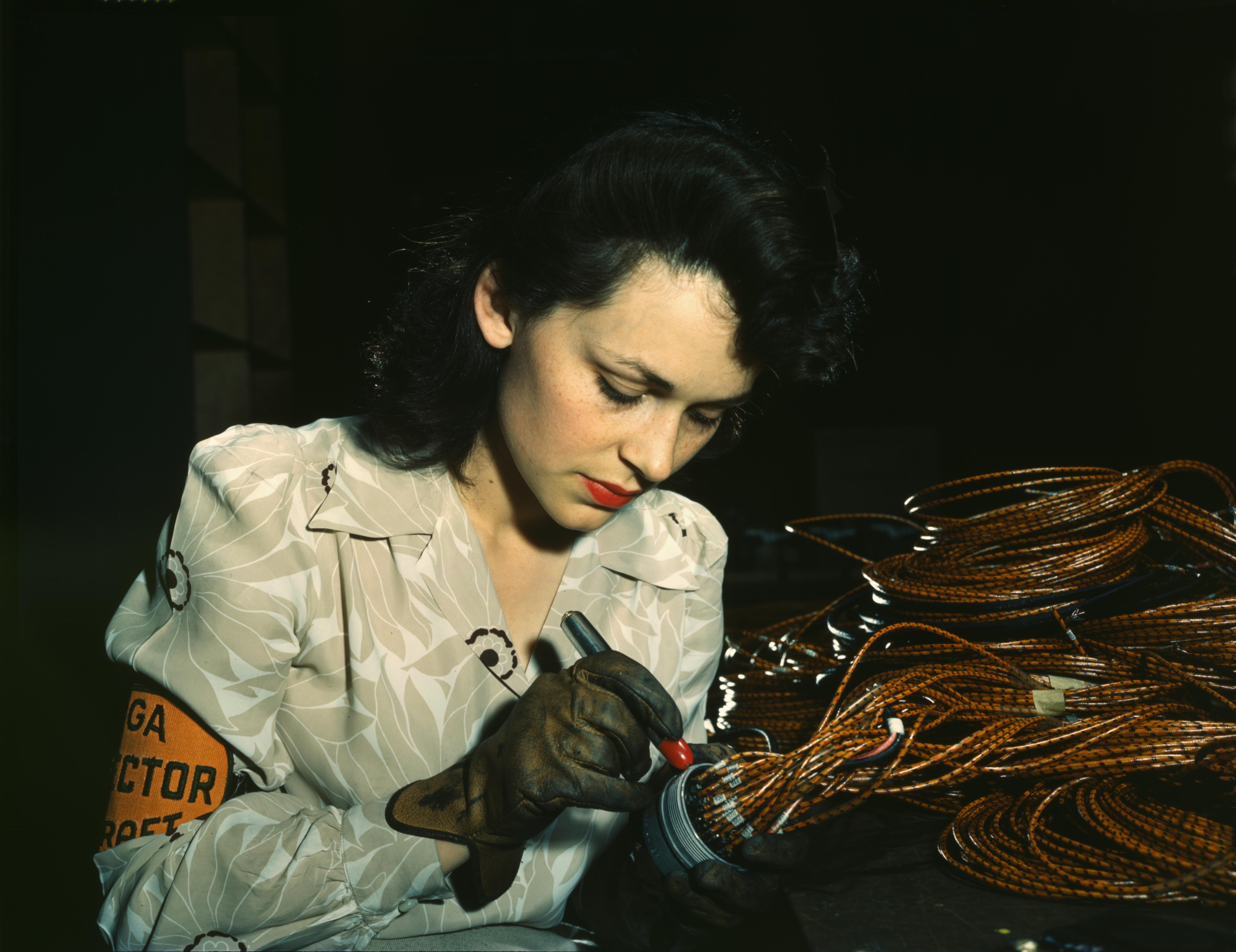 Woman aircraft worker checking assemblies at the Vega Aircraft Corporation in Burbank, California. Photograph by David Bransby, June 1942.
