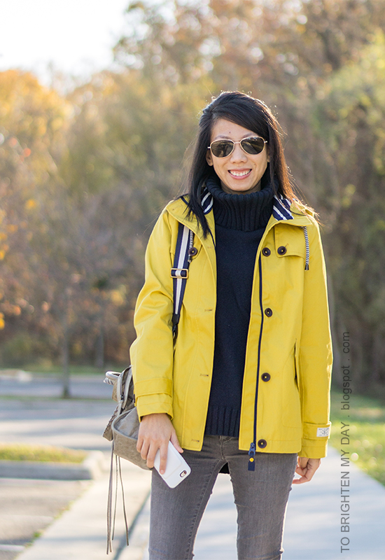 yellow rain jacket, navy turtleneck sweater tunic, gray skinny jeans, gray tote with stripe strap