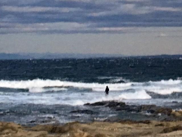 高波の中釣りをする人