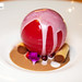 Pomegranate ice sphere on gianduja cream and cannellloni filled with salty pine seed chantilly