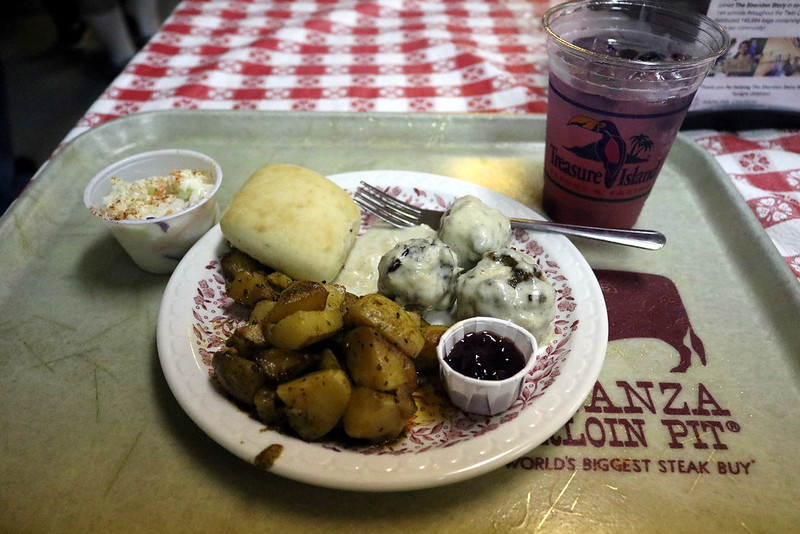 a white tray with a plate of three meatballs, white gravy, a roll, potatoes, a cup of coleslaw off to the left, and a glass of an iced purple beverage