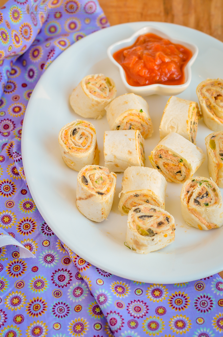 A platter full of pinwheels with a bowl of salsa on the side.