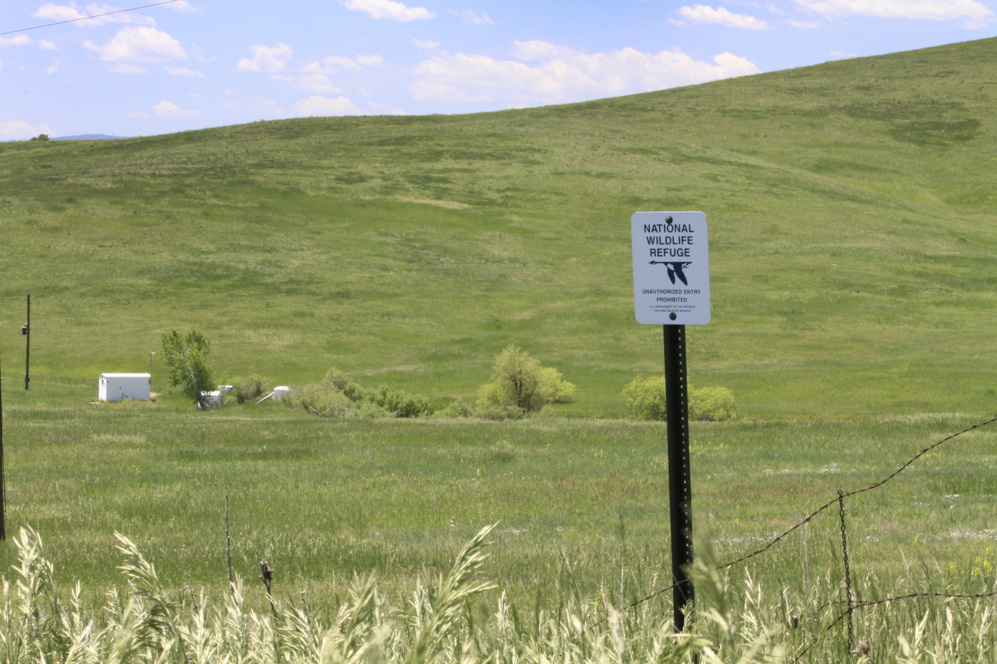 A white sign announces the border of the Rocky Flats National Wildlife Refuge. In the distance, in a grassy field beside a creek, white buildings and other infrastructure perform ongoing monitoring.