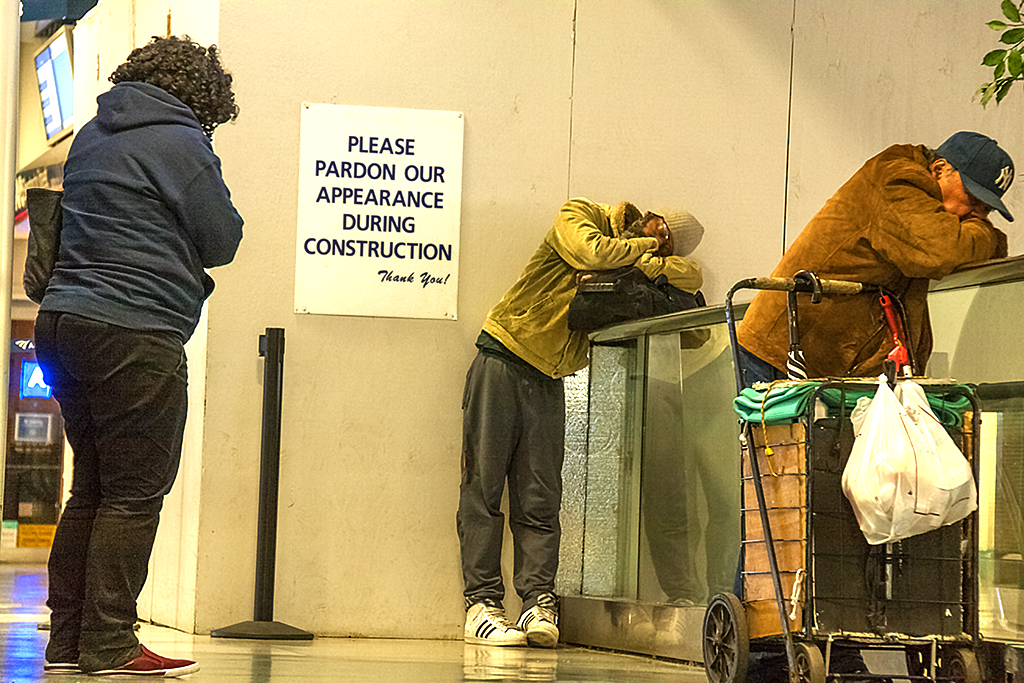 Three homeless people sleeping while standing up in Penn Station--Manhattan