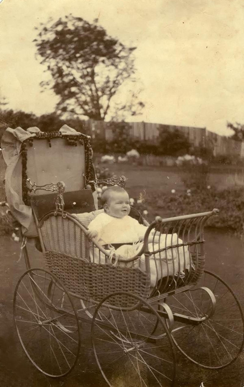 1914. Baby Charmain, aged 7 months seated in an elaborate cane pram