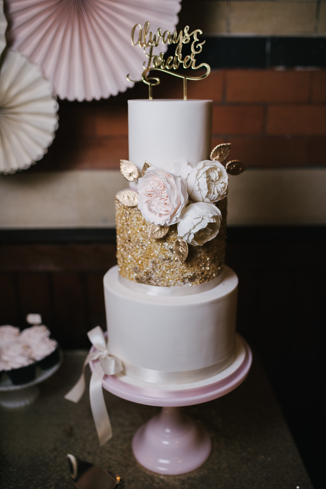 picture of a three tier wedding cake, white with one gold glitter layer and pink ribbon