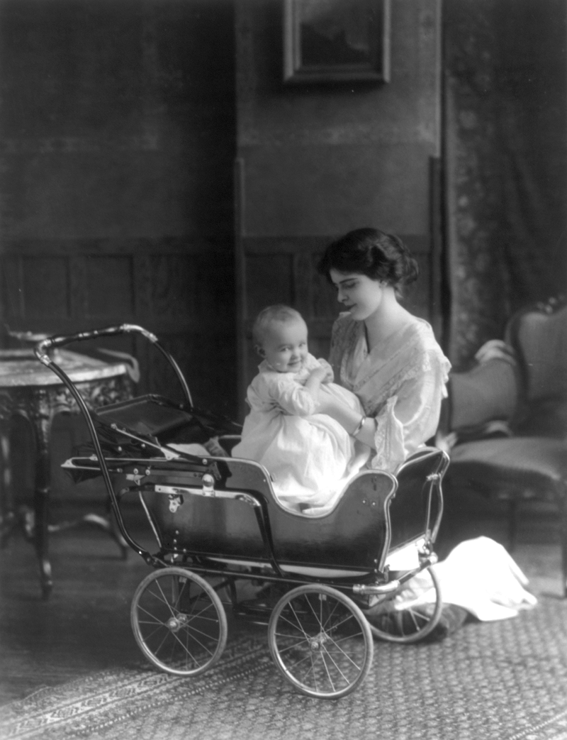 Woman and infant posed with a baby carriage, 1913
