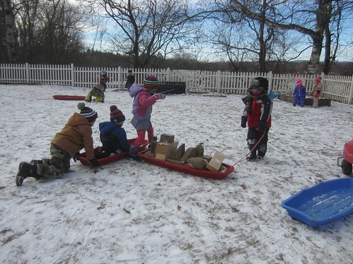 kids and blocks in sleds