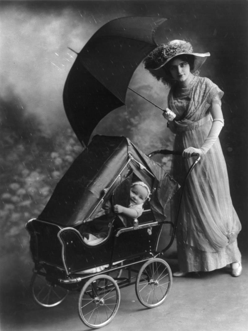 Woman, holding umbrella, pushing baby in carriage equipped with rain cover