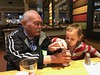 Sawyer asks to sit next to Grandpa Jim and Jim helps him get ice out of his kids cup