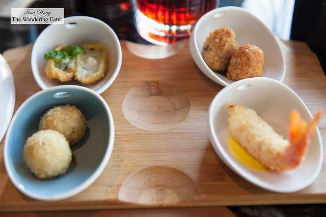 Selection of four cicchetti - Fried courgette blossom stuffed with mozzarella and anchovies; fried and stuffed rice ball, Roman style; crunchy prawn; fried and stuffed rice ball with tomato dip