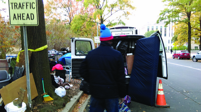Photo of a van stuffed full with it's back doors open. A mattress leans against one door and a man carrying items toward it.